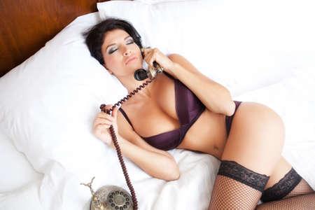 Sexy sinnliche Frau, die einen erotischen Anruf im Bett