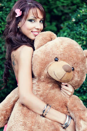 adult toys: Happy cute young woman and her teddy bear Stock Photo