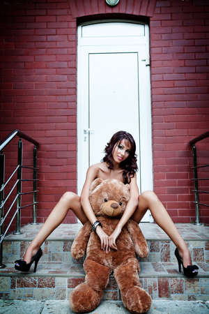 outdoor glamour: Sexy young woman with her teddy bear Stock Photo