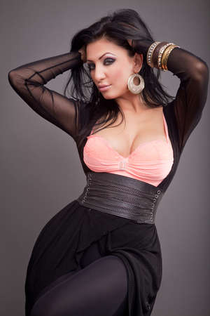 voluptuosa: Una mujer hermosa sexy posando sobre fondo oscuro Foto de archivo