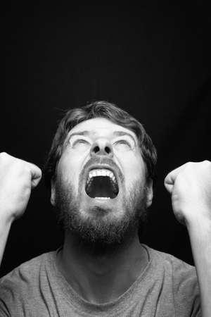 caras de emociones: Grito de hombre rebelde enojado sobre negro Foto de archivo