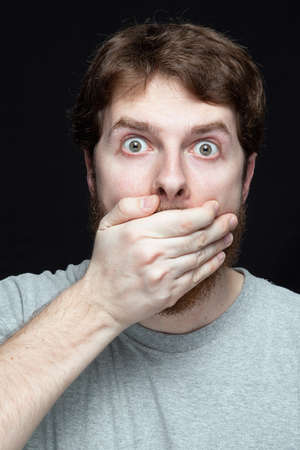 shocked face: Secret concept - young man amazed by gossip news Stock Photo