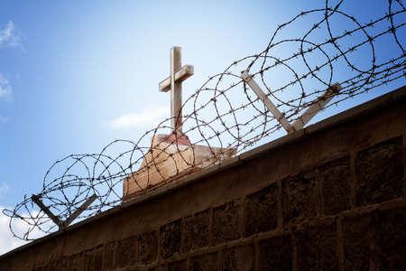 Krieg und Religion Konzept - Kreuz und Stacheldraht über blauen Himmel