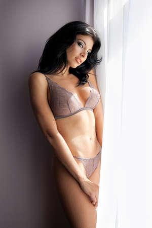 Sinnlich sexy Frau posiert in Dessous in der Nähe hellen Fenster