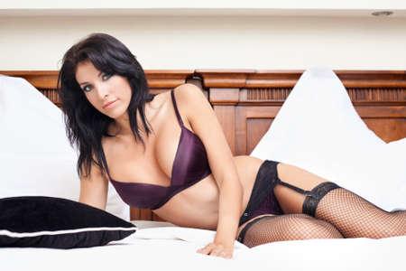 Schöne Frau in sexy Dessous posiert auf Bett