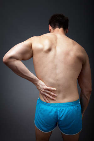 muscle tension: Back pain concept - man holding his sore torso