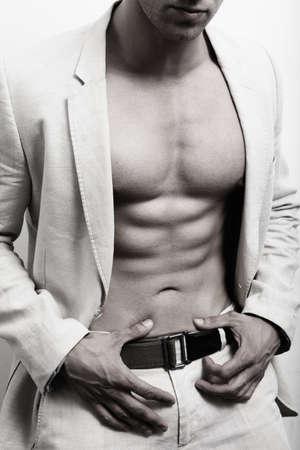 Muskulöser Mann mit sexy Bauchmuskeln und Anzug über weißem Wand