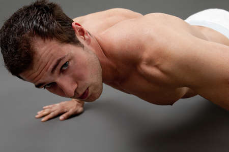 Fitness concept - sexy muscular man doing push-ups photo