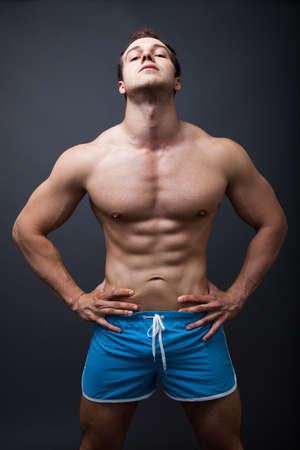 Sexy Mann mit muskulösen athletischen Körper posiert im Studio