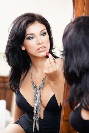 Sexy sinnliche Frau, die Anwendung Lippenstift in den Spiegel