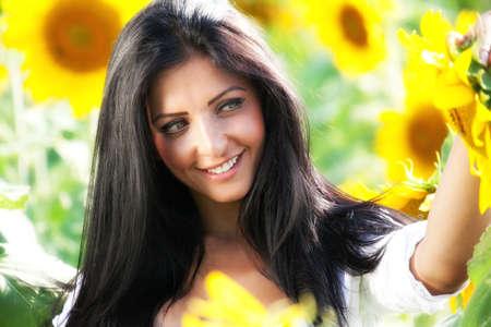 Happy cute woman in sunflower field photo