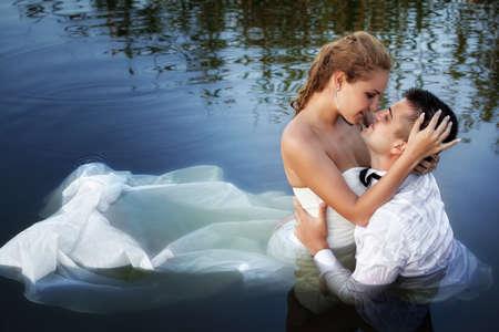 Liebe und Leidenschaft - Kuss der verheirateten jungen Paar in Wasser