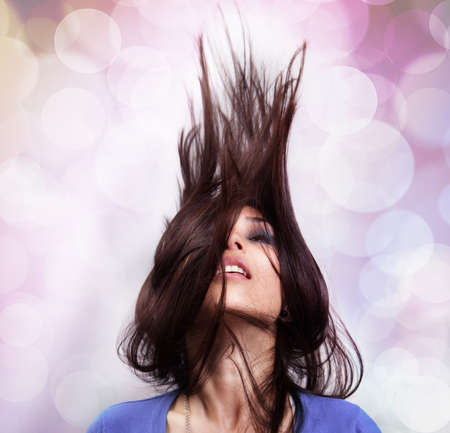 Dance and party concept - woman with hair in motion photo