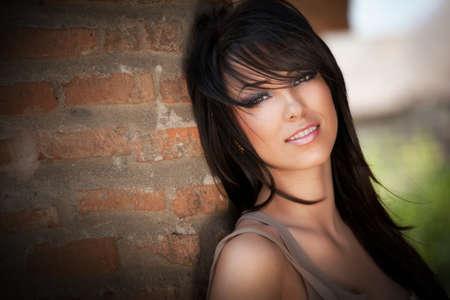 Nette schöne junge Frau mit langen dunklen Haaren