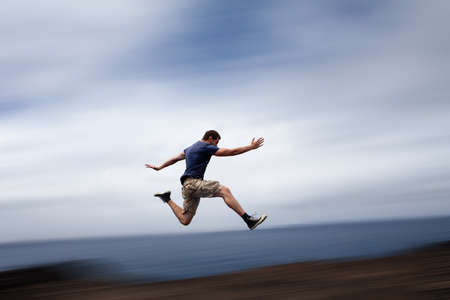 Sport and energy concept - athletic man running fast photo