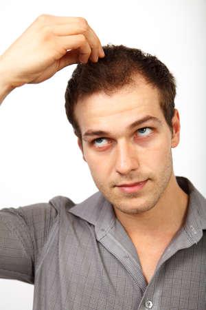 calvicie: Concepto de la p�rdida de pelo - hombre joven preocupado por la calvicie aislado en blanco Foto de archivo