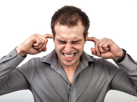 irritating: Too much noise or pressure concept - man covering ears for some silence Stock Photo