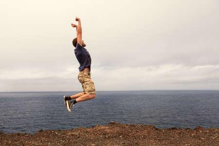 ocea: Success or win concept - joyful man jumping outdoor Stock Photo