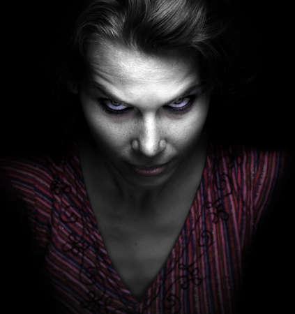 Scary mujer malvada fantasmagórica en la oscuridad