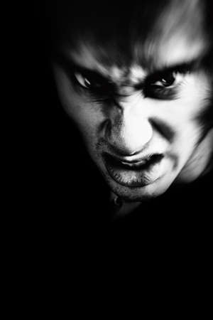 male killer: Evil face of scary angry man in the dark Stock Photo