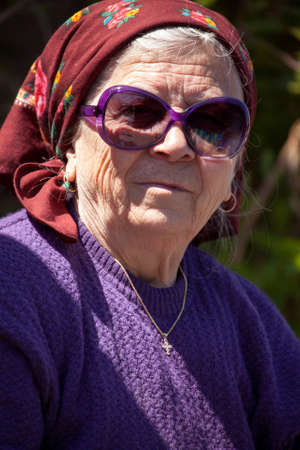 Funny senior woman with sunglasses outdoors photo