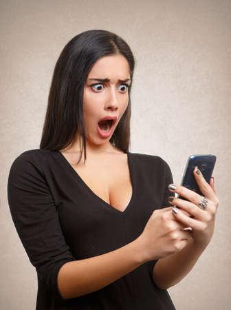 asustado: La mujer joven sorprendido por la noticia de teléfono móvil o un mensaje