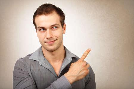 viso uomo: Felice giovane isolato che indica barretta Archivio Fotografico