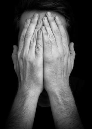 hands covering face: Depression concept � man covering face with hands Stock Photo