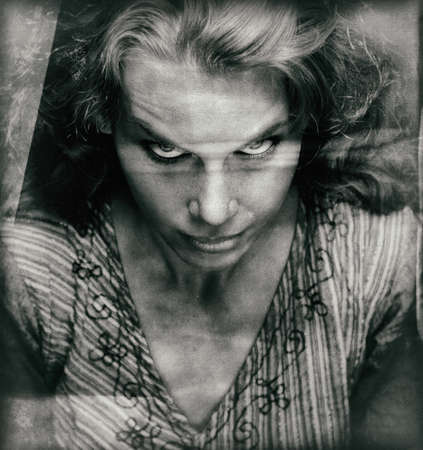 Vintage portrait of scary woman with evil looking face photo