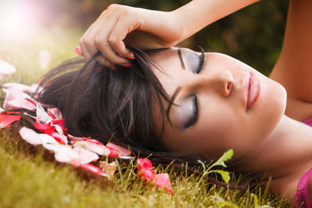 Beauty portrait of young woman with flower petals near face photo