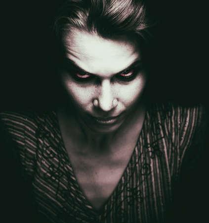 Gesicht der Frau mit unheimlich böse Augen in der Dunkelheit