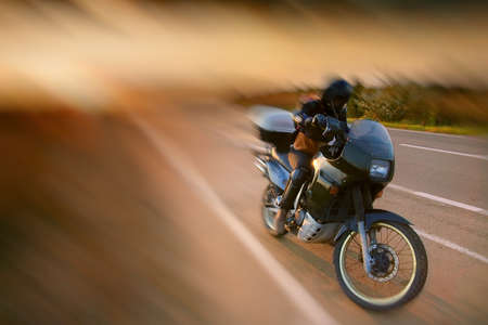 touring: Biker and motorcycle on the road at sunset Stock Photo