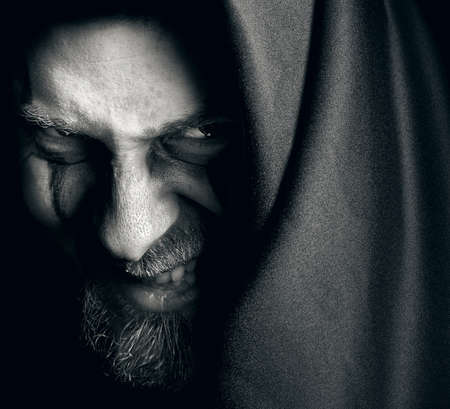 diabolic: Evil sinister man with malefic grin Stock Photo