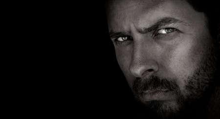 Low-key portrait of scary man with evil eyes Stockfoto