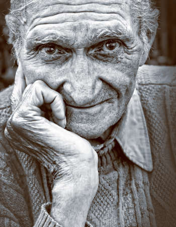 Old senior man with wrinkled face and expressive eyes photo