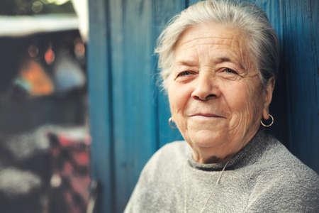 Happy old senior woman smiling outdoor portrait photo