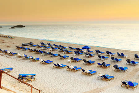 Chairs and umbrellas on beach resort in Greece, at sunset