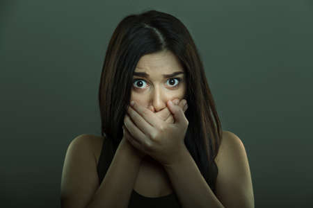 Scared woman with fear expression and hands covering mouth