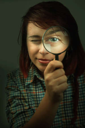 Funny spy young woman looking through magnifying glass