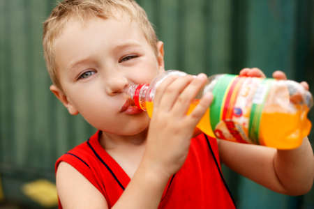 Child drinking unhealthy sweet bottled soda Stock Photo