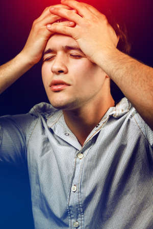 Tired stressed young man suffering from headache or hangover Stock Photo