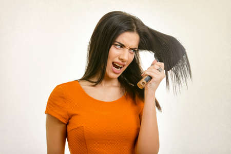 Tangled messy hairstyle problem. Young woman brushing her damaged hair Stock Photo
