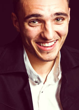 Portrait of laughing happy young man over black background Stock Photo