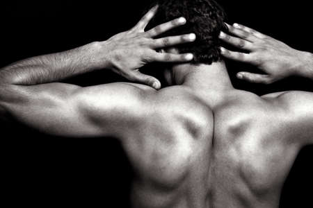 Back muscles of lean fit athletic man fashion posing over black background Stock Photo