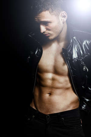 Attractive sexy masculine guy posing fashion over dark background Stock Photo