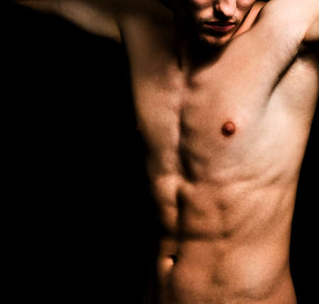 Naked young male body over black background