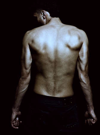Sexy male with muscular lean back posing fashion over dark background Stock Photo