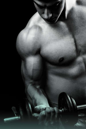 Muscular male bodybuilder doing biceps curl with dumbbell over dark background Zdjęcie Seryjne