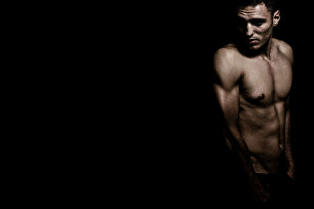 Shirtless athletic masculine guy over dark black background Zdjęcie Seryjne - 134778604