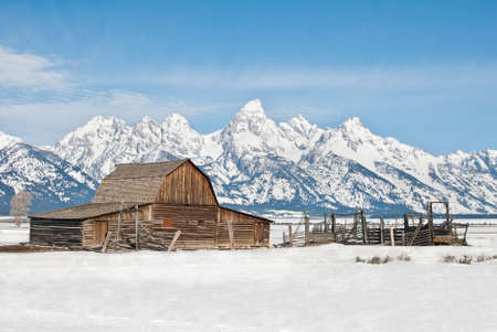 Spring on an old barn and corral stand on a Wyoming ranch with the Teton Peaks towering in the background. photo